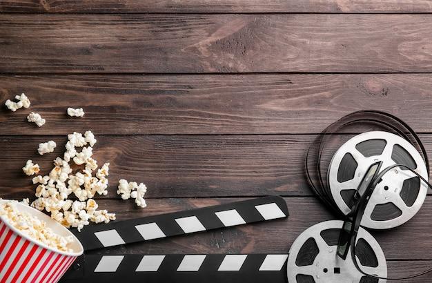 Gustosi popcorn, bobina di film e assicella su legno