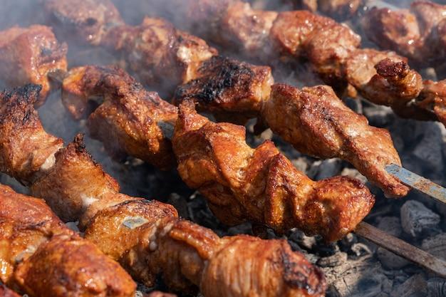 Gustoso shish kebab di maiale cucinato su spiedini alla griglia a carbone