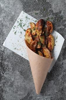 Gustosi spicchi di patate avvolti in carta da imballaggio kraft marrone. vista dall'alto