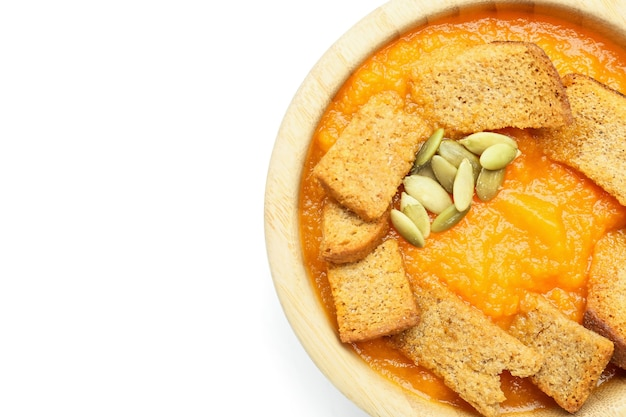 Gustosa zuppa di crema di zucca in ciotola su bianco