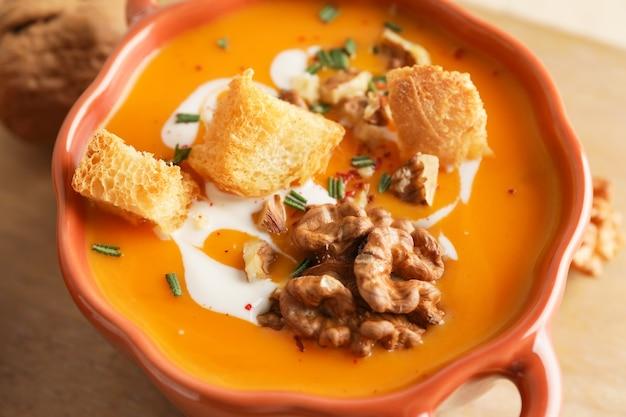 Gustosa zuppa di crema di zucca in vaso, primo piano