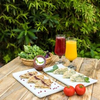 Gustoso qutab, pasto azero con yogurt, succo sul piatto di legno Foto Premium