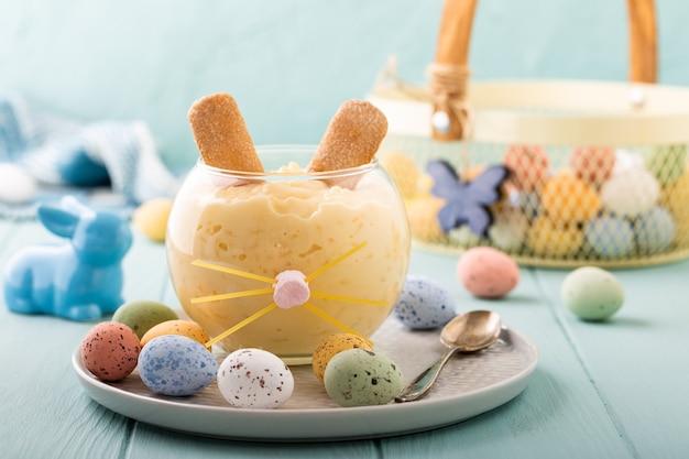 Dessert gustoso budino di riso decorato di coniglietto di pasqua con uova di quaglia colorate. holiday helthy food concept con copia spazio