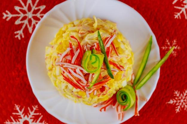 Gustosa insalata con polpa di granchio, mais, cetriolo e uova per la cena di natale. vista dall'alto.