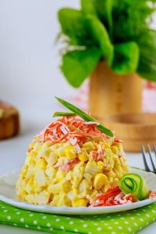 Gustosa insalata con polpa di granchio, mais, cetriolo e uova. foto verticale.
