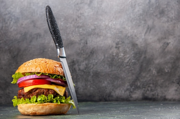 Gustoso panino e coltello sul lato destro su una superficie di colore misto scuro con spazio libero