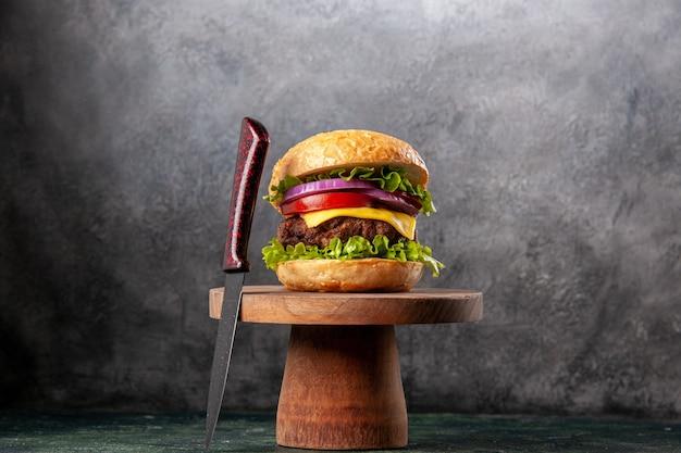 Panino gustoso e forchetta rossa su tagliere di legno su superficie di colore misto scuro con spazio libero