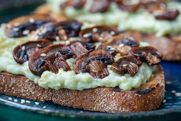 Gustoso panino con purè di avocado verde, funghi fritti e semi di sesamo in un piatto su un tavolo, primo piano. cibo vegetariano