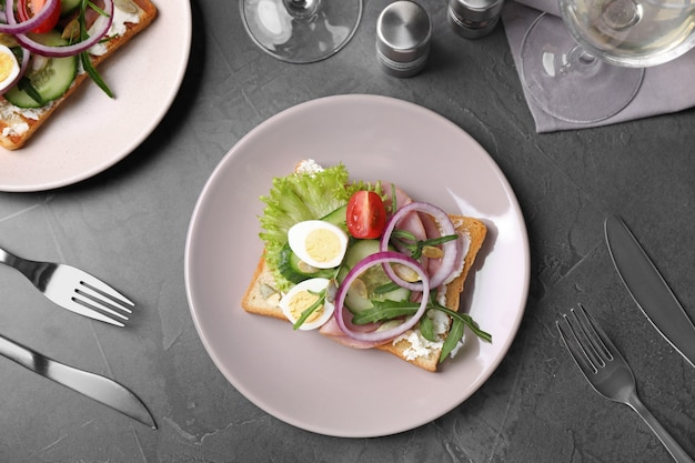 Gustoso panino con prosciutto e uova di quaglia servito su tavola grigia, piatto disteso
