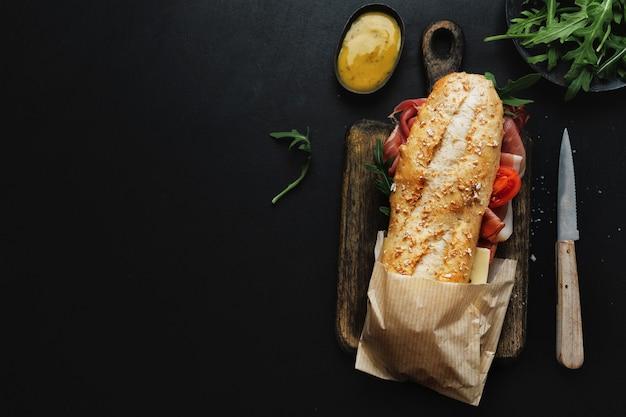 Gustoso panino con carne e verdure sul tavolo scuro. vista dall'alto.