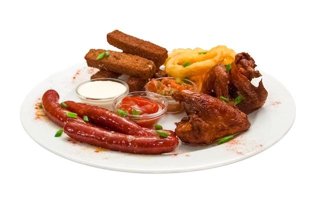 Gustoso set di snack alla birra su un piatto tagliatelle di pollo salsicce bavaresi anelli di calamari con salse
