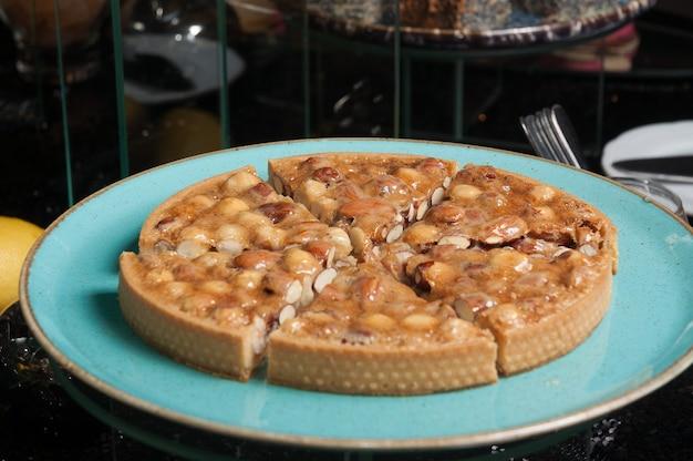 Gustosa torta di pasta frolla con noci e caramello su un piatto blu su uno sfondo scuro