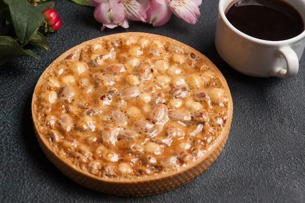 Gustosa torta di pasta frolla con noci e caramello con una tazza di americano