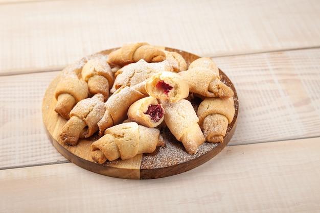 Gustoso biscotto di pasta frolla con marmellata sulla scrivania in legno rotondo