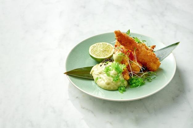 Gustose patatine fritte di gamberetti, impanate con salsa bianca, caviale di tobiko verde e lime depositate in un piatto verde su un tavolo di marmo. gamberi in stile asiatico. ristorante di pesce