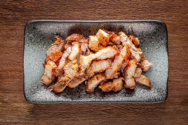 Porco fritto della fetta saporita in piatto ceramico rettangolare su fondo di struttura di legno naturale rustico, vista superiore
