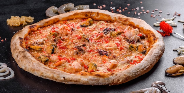 Gustosa pizza a fette con frutti di mare e pomodoro su sfondo nero. cucina mediterranea