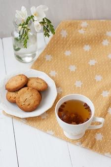 Spuntino gustoso. tazza di tè e un piatto di biscotti.