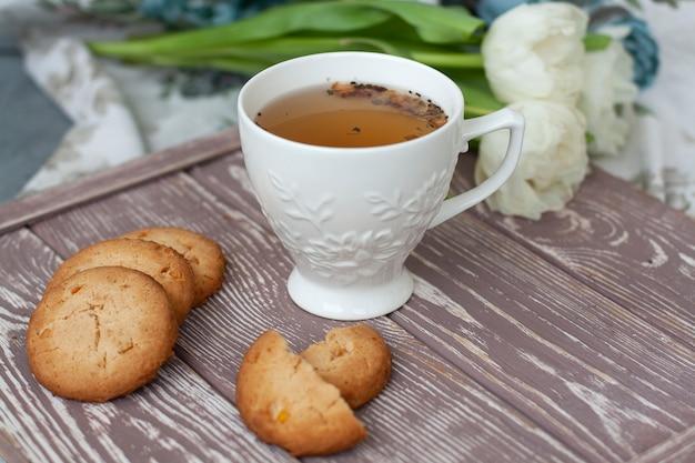 Spuntino gustoso. tazza di tè e una pila di biscotti.