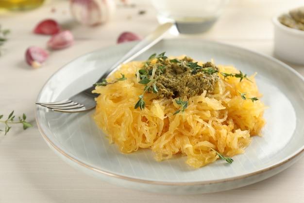 Zucca di spaghetti saporita con salsa al pesto e timo sulla tavola di legno bianca