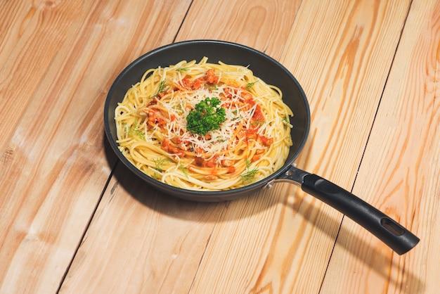 Gustosi spaghetti con salsa di pomodoro e carne in padella sul tavolo di legno.