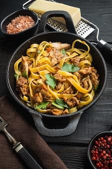 Gustoso spezzatino di coniglio piccante con set di tagliatelle di pasta o pappardelle, in padella o pentola in ghisa, sul tavolo di legno nero