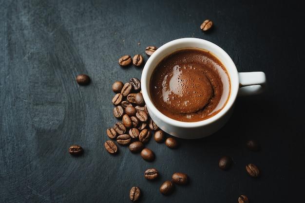 Gustoso caffè espresso fumante in tazza con chicchi di caffè.