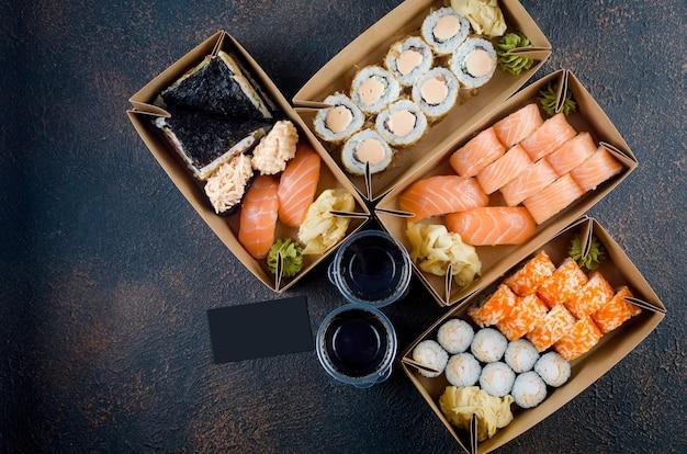 Gustosi rotoli di sushi in scatole di carta kraft usa e getta, salse sul tavolo scuro. servizio di consegna concept cibo giapponese in contenitore ecologico. disposizione piatta, modello di modello con posto per il testo, imballaggio a zero rifiuti