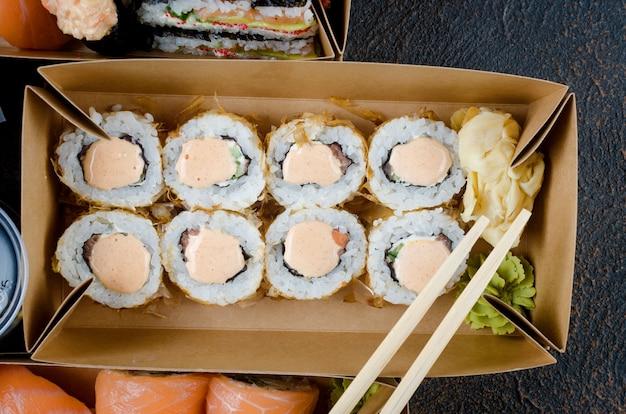 Gustosi rotoli di sushi in scatole di carta kraft usa e getta, salse sul tavolo scuro