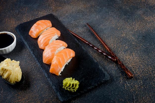Gustosi rotoli di sushi impostati su lastra di pietra con salse