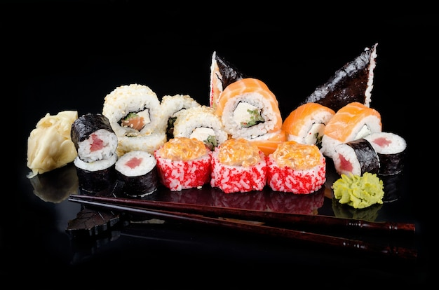 Gustosi rotoli di sushi con salse, bacchette, zenzero sul tavolo