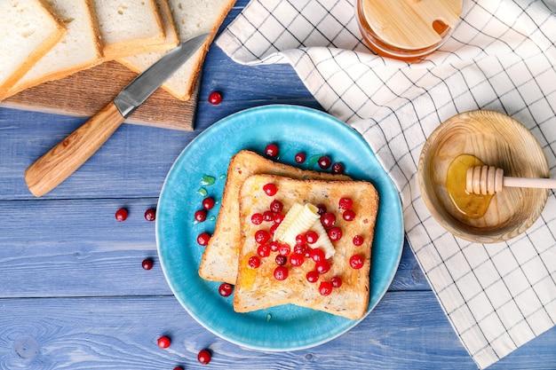 Gustoso pane tostato con miele, burro e frutti di bosco sul tavolo