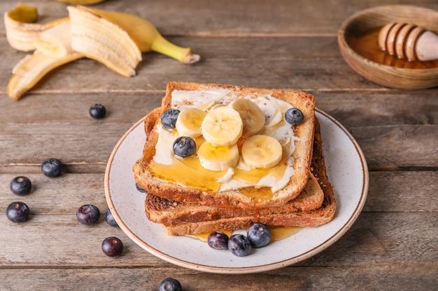 Gustoso pane tostato con miele, burro e frutta sul piatto