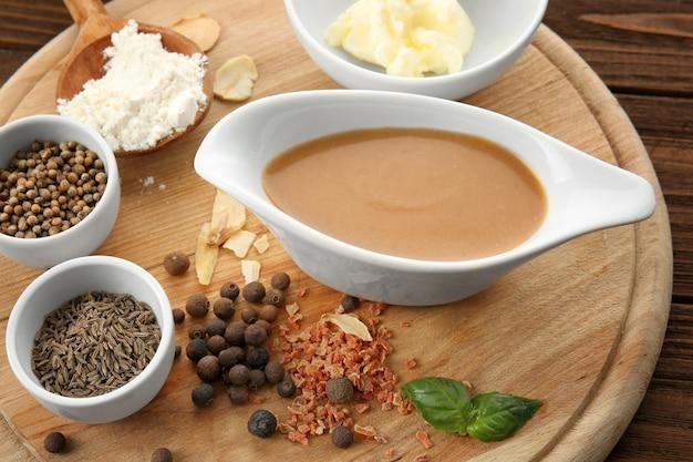 Gustoso sugo di tacchino in salsiera e spezie su tavola di legno