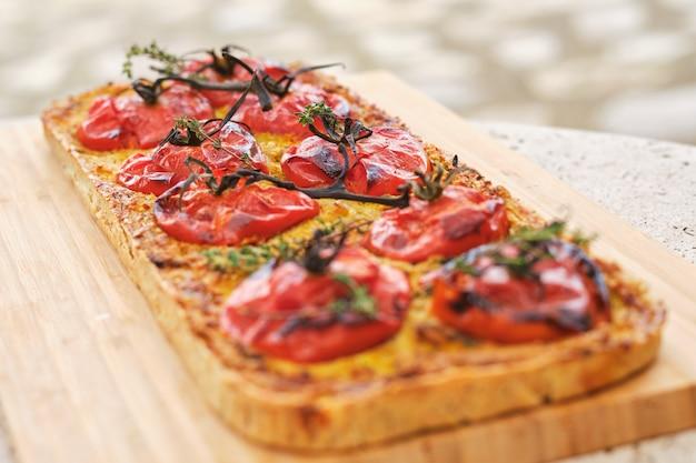 Gustosa pizza vegetariana con pomodorini sul tagliere