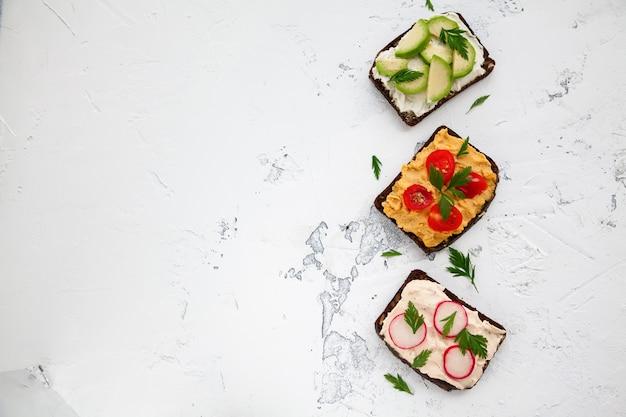 Gustosi toast vegetariani di pane di segale con ricotta, hummus, avocado, ravanello e pomodoro