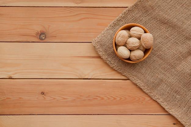 Noci saporite su un tavolo di legno su un piatto. immagine rustica piatta