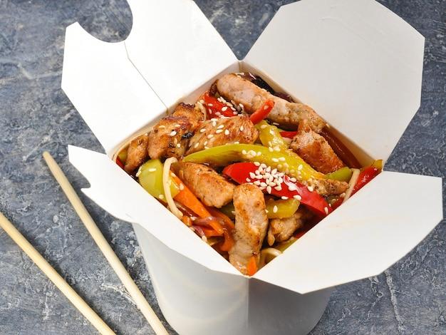Gustosi noodles wok con carne di maiale e verdure in una scatola su uno sfondo grigio