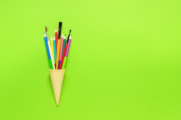 Tationery ha colorato il pennello delle matite nel cono gelato della cialda Foto Premium