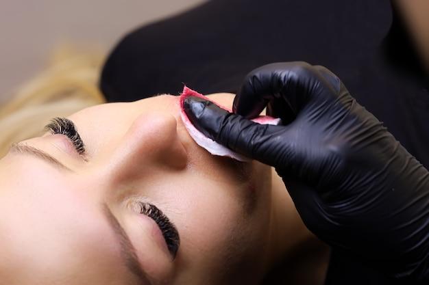 Un tatuatore in guanti neri rimuove il pigmento rosso in eccesso per i tatuaggi dalle labbra della modella