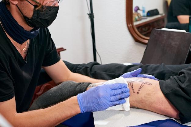 Il tatuatore in guanti blu che pulisce il tatuaggio appena completato sulla gamba di un uomo