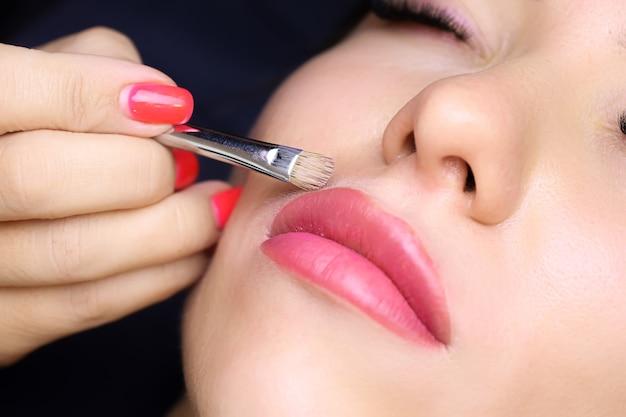 Il tatuatore tiene un pennello in mano e spalma un fondotinta vicino alle labbra correggendo il lavoro finito del tatuaggio