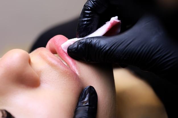 Il tatuatore indossa guanti neri, le modelle ospiti cancellano il pigmento con le dita