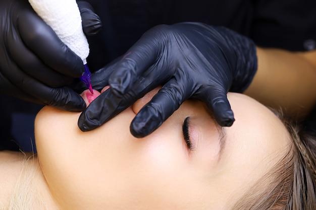 Il tatuatore realizza il trucco permanente delle labbra della modella con il labbro inferiore