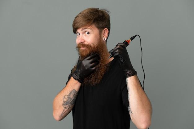 Tattoo artista redhead uomo isolato su sfondo blu pensando