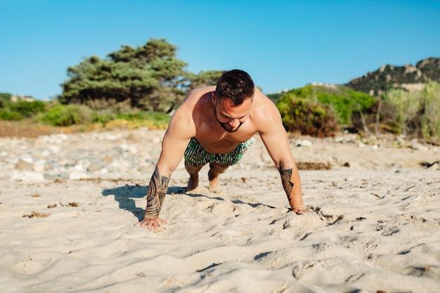 Uomo tatuato che fa un push up in spiaggia