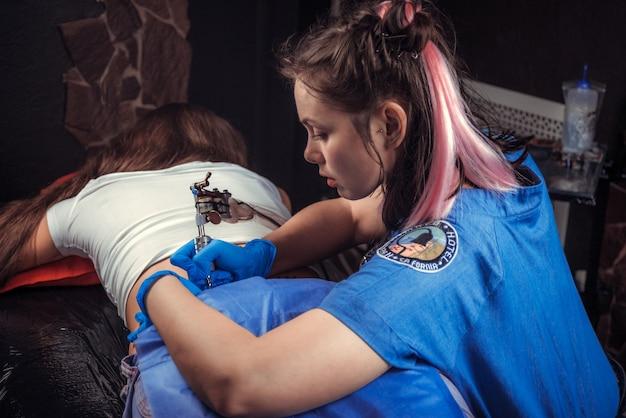 Il maestro del tatuaggio dimostra il processo per ottenere un negozio di tatuaggi.