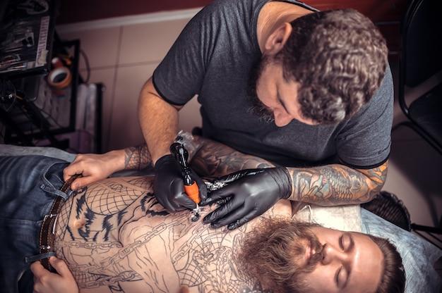 Il maestro del tatuaggio fa le foto del tatuaggio nel negozio di tatuaggi