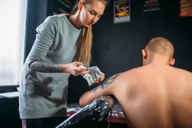 Il maestro del tatuaggio spruzza il congelamento sulla pelle dei clienti