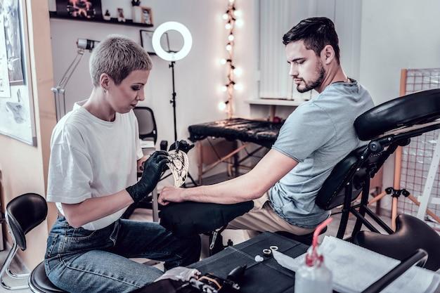 Maestro del tatuaggio che lavora. attenta donna attenta che attacca schizzo speciale con l'immagine del futuro tatuaggio su di esso sulla mano del cliente